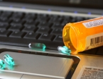 Pills spilling from pill bottle onto laptop keyboard